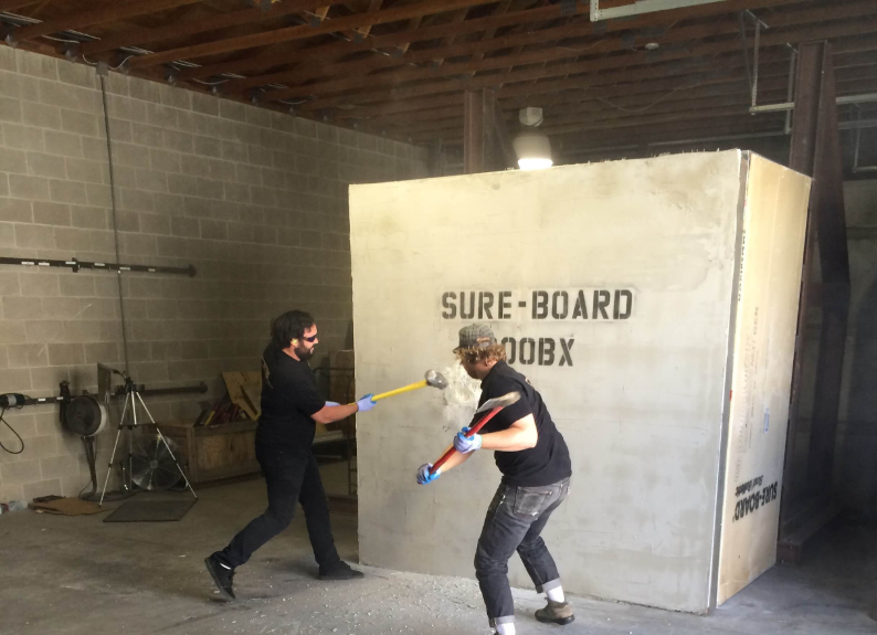 2 Men testing sureboard wall with sledgehammers