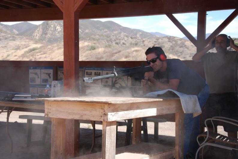 Man firing 50. caliber high powered rifle at sureboard
